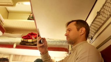 A person uses a smartphone in a compartment of a passenger train. 4k