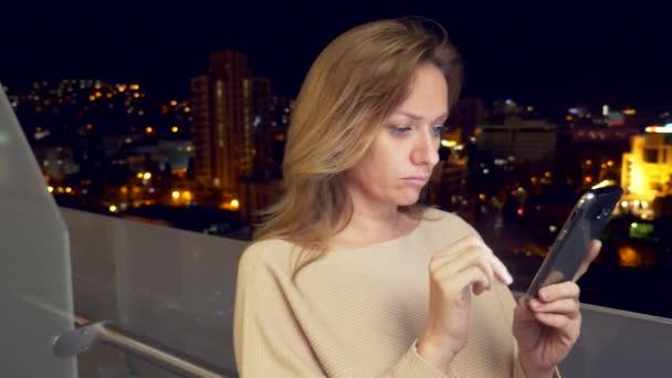 junge, glückliche Frau mit Smartphone auf dem Balkon in der Stadt in der Nacht, 4k