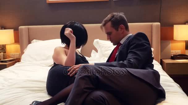 coppia, uomo daffari maschio e donna castana con i capelli corti è possibile bere alcolici sul letto nella camera dalbergo. 4k
