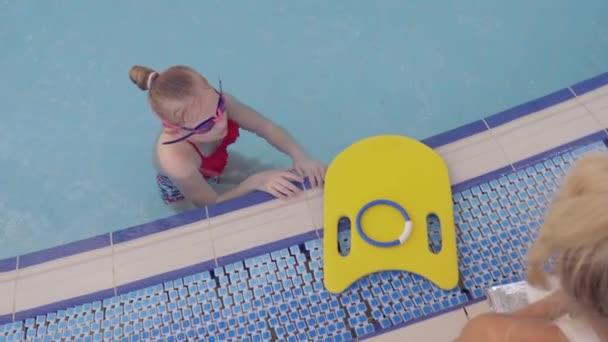 dívka, plavčík, provádí výcvik v bazénu s dětmi. 4k, pomalý pohyb