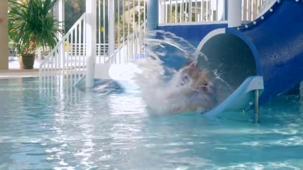 children swim in the pool, roll down from the water slide 4k, slow-motion