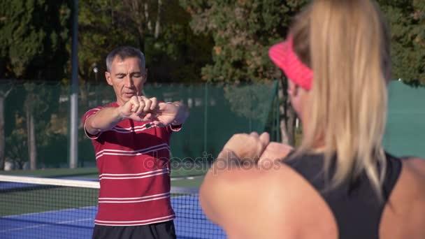 Spieler wärmen sich vor einer Partie Tennis auf. ältere Männer und Frauen beim Tennisspielen. 4k