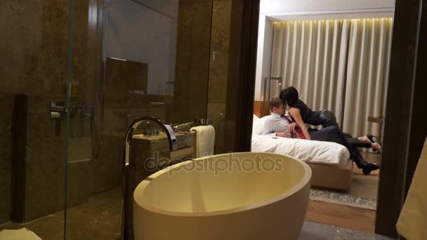 Paar, männlicher Geschäftsmann und brünette Frau mit kurzen Haaren in Lederhose und Schwertgürtel verwenden eine Peitsche und Handschellen für sexuelle Zwecke auf dem Bett in einem Hotelzimmer. 4k