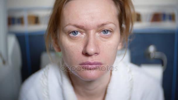 portrét. bledá žena sedí na záchodě na záchodě. 4k, rozostřené pozadí