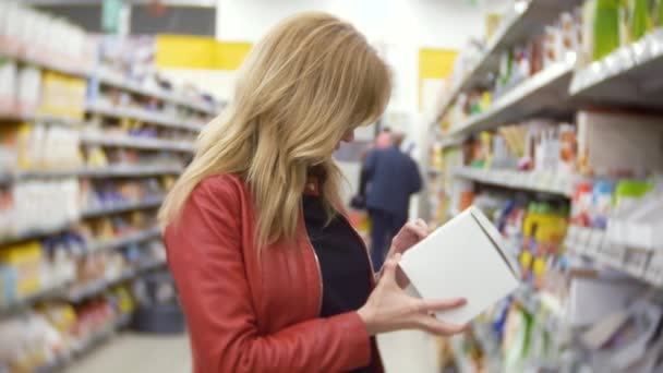 Young woman choosing food in grocery store, woman shopping in supermarket. 4k, background blur