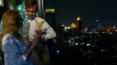 Happy couple hugging, kissing and drinking cocktails on the terrace of the bar overlooking the skyscrapers, at night, 4k, blur background. romantic date, honeymoon.