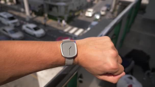 close-up . wristwatch on a mans hand, against a background of a city street with high traffic. Slow motion, blur background. 4k