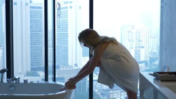 Krásná žena sama otřít ručníkem v luxusní koupelnu s oknem. Koncept způsobu života a krásy. pohled z okna na mrakodrapy. 4k