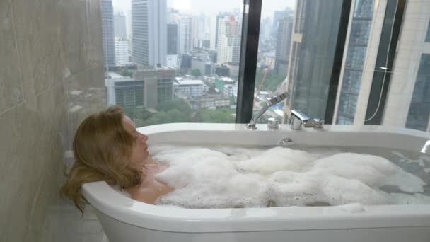 Krásná žena se těší relaxační koupel v luxusní koupelnu s oknem. Koncepce péče o životní styl a krása. pohled z okna na mrakodrapy. 4k