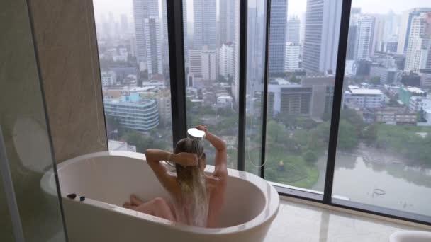 Krásná žena myje vlasy v luxusní koupelnu s oknem. Koncept způsobu života a krásy. pohled z okna na mrakodrapy. 4k