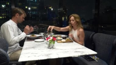 Happy couple talking and having dinner in a bar overlooking skyscrapers, in the evening, 4k, blur background