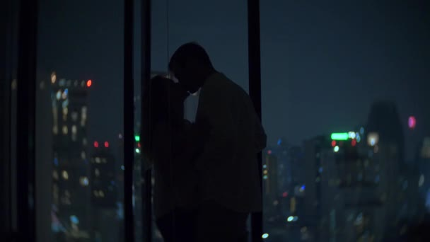 a young couple is kissing on the background of a panoramic window overlooking the city