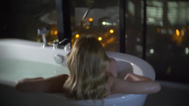 Krásná žena se těší relaxační koupel v luxusní koupelnu s oknem v noci. Koncept způsobu života a krásy. pohled z okna na mrakodrapy. 4k