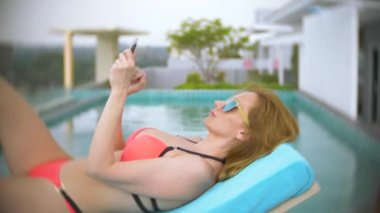 a woman in a pink bikini by the pool on the roof, a girl sunbathing on a deckchair and using the phone. 4k, slow motion