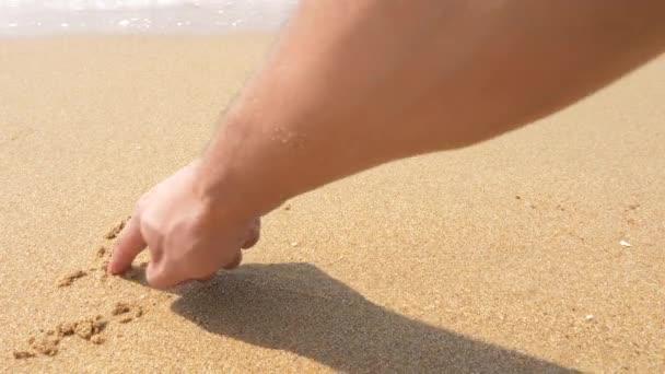 Mořská vlna maže nápisy napsané na písku. 4k, pomalý pohyb, pohled shora. vzorec E M C náměstí