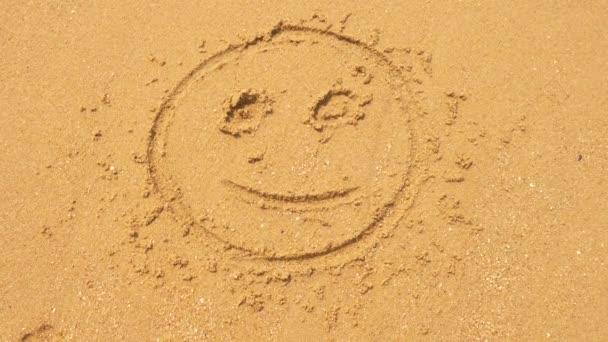 Mořská vlna maže nápisy napsané na písku. 4k, Zpomalený pohyb, pohled shora. smajlík