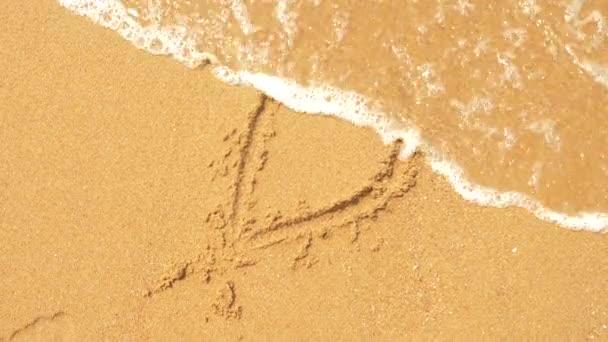 Mořská vlna maže nápisy napsané na písku. 4k, pomalý pohyb, pohled, písmeno d shora