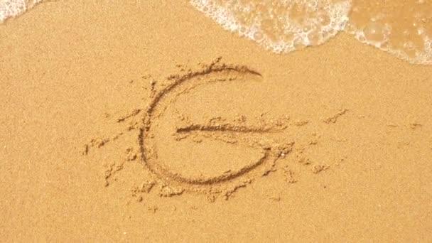 Mořská vlna maže nápisy napsané na písku. 4k, pomalý pohyb, pohled shora. písmeno g