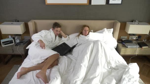 Giovane coppia sdraiata a letto con il computer portatile, chat ...