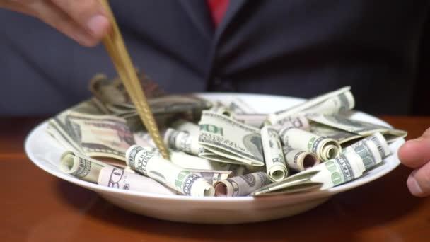 Die Hände eines Geschäftsmannes mit Essstäbchen und Dollarrollen. Dollar essen. 4k.