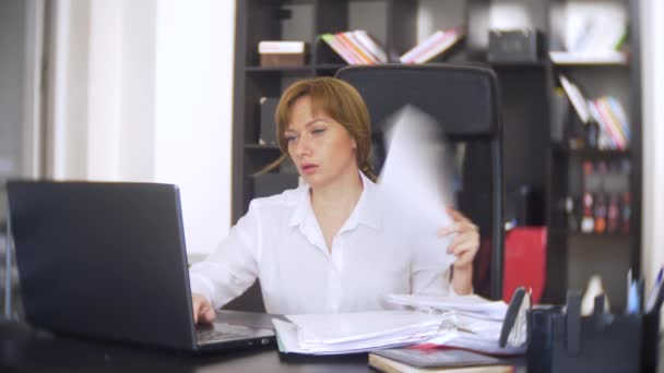a businesswoman who scans documents, frowns, using a laptop, does not perform an urgent task in the office, there is not enough time, 4k. the office is hot, the air conditioning is not working