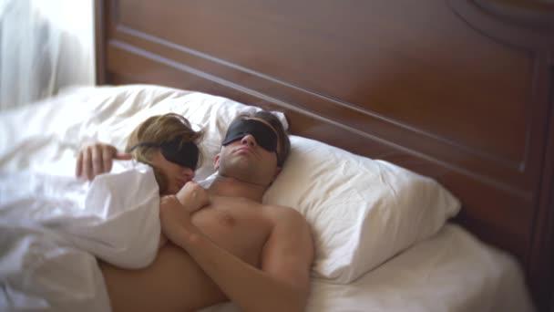 egy házaspár nő és egy férfi egy maszkot, az alvás, alvás ágy, egy párna napközben. 4k