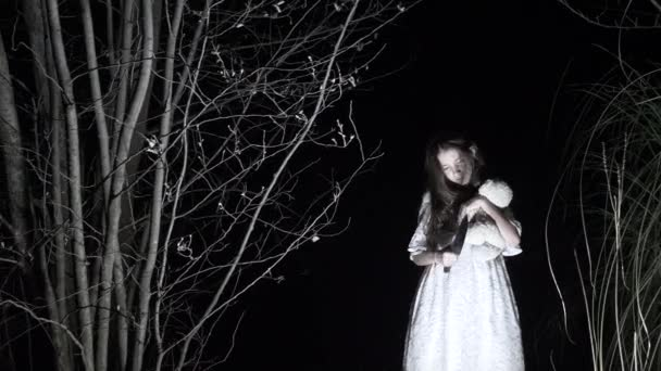 Ein kleines Gespenst Mädchen mit langen schwarzen Haaren, in weiß, Wanderung durch den Wald mit einem Messer und einem Stofftier. 4k