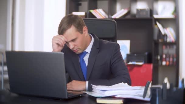 ein Geschäftsmann, der Dokumente scannt, runzelt die Stirn, mit einem Laptop, führt keine dringende Aufgabe im Büro aus, es ist nicht genug Zeit, 4k. das Büro ist heiß, die Klimaanlage funktioniert nicht