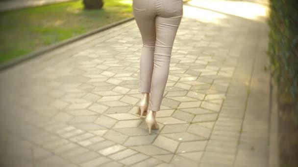 štíhlé ženské nohy v béžové kalhoty a boty s vysokými podpatky se projít v parku, na jasný slunečný den. 4k, pomalý pohyb