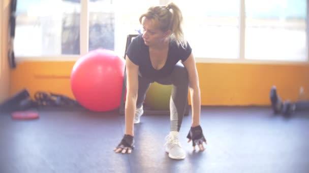 Žena pracující v tělocvičně. 4k, rozostřené pozadí