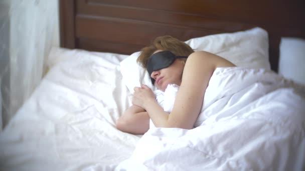Junge Frau in einer Maske zum Schlafen, schlafen im Bett auf einem Kissen am Tag. 4k.