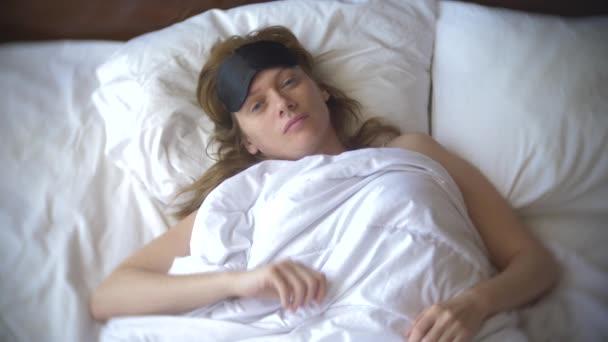 Fiatal nő egy maszk, alszik, alszik az ágyban, a párna, a nappali. 4k.