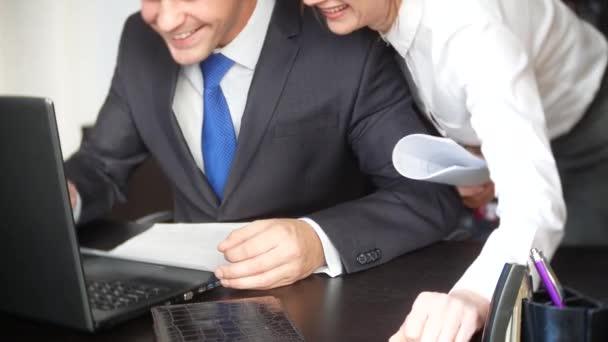 muž a žena v přísně obleky při práci na notebooku, dokumentů, diskuse v úřadu. 4 k. smějí se při pohledu na monitor notebooku