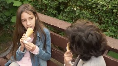 cute teenagers, boy and girl eating ice cream in the park and talking. 4k