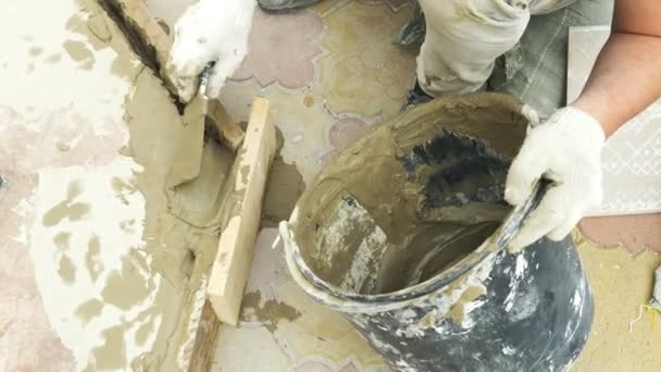 spatula and bucket with mortar on the construction site. the builder finishes the surface with plaster. 4k.