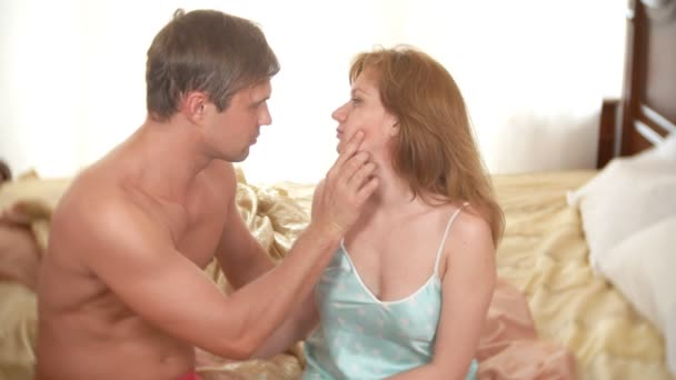 adult man and woman tenderly embracing sitting in bed. prilyudiya. 4k.