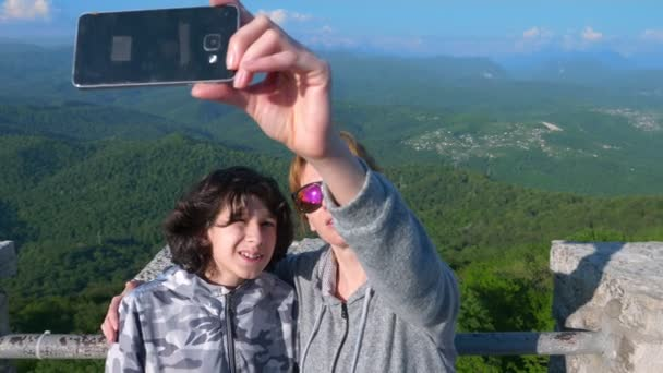 a woman and her son a teenager doing sefi with a view of the Magnificent Mountains. 4 k. Slow shooting