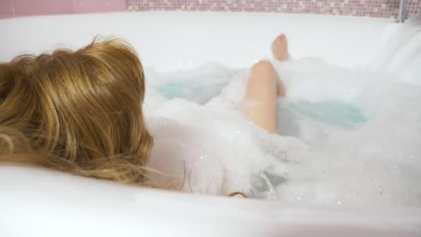 Krásná mladá žena relaxuje v lázni s hydromasáží, na modrém pozadí. Koncepce: lázeňské procedury, masáž těla, masáž, spa smetana, relaxace, vodních procedur. 4k, zpomalené. pohled shora