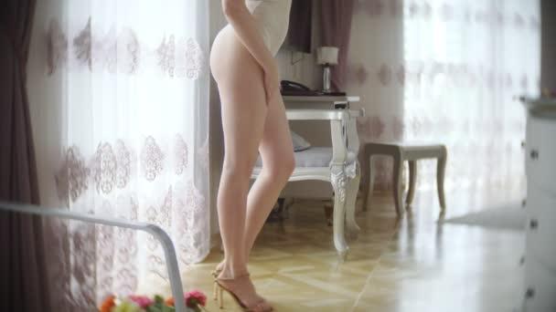 Hezká žena v béžové těle pózuje v svůdné pózy. v pokoji s elegantním interiérem. velké štíhlé tělo a velká prsa. 4k