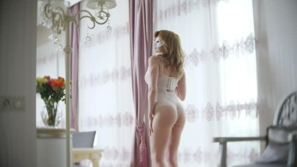 Szép nő, bézs szervezetben, csábító vet pózol. egy szobában elegáns belsővel. nagy, vékony test és a nagy mellek. 4k