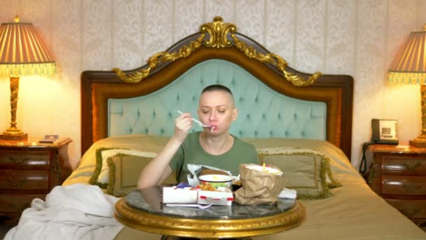 hungry bald girl in a khaki shirt eating fast food sitting in a luxurious interior on the bed