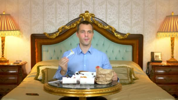 Handsome businessman is eating fast food sitting on the bed in a luxurious interior.