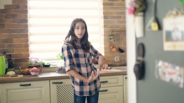 krásná brunetka teen dívka tanec zábava v kuchyni.