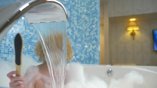 v ohniskové vodě tekoucí z kohoutku. na pozadí Mladá krásná žena v luxusní koupeli s hustou pěnou leští pokožku nohy pumpou. Koncept péče o tělo.