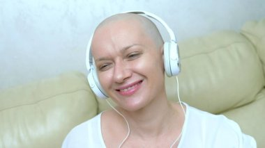 close-up. a bald woman in headphones listens to music and moves her head to the beat of the music.