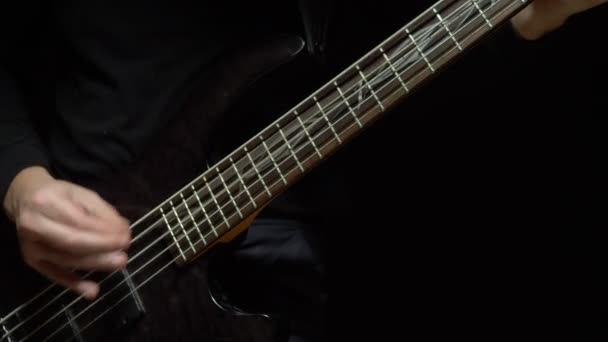 Az ember basszusgitározik. Sötét háttér. lassulás