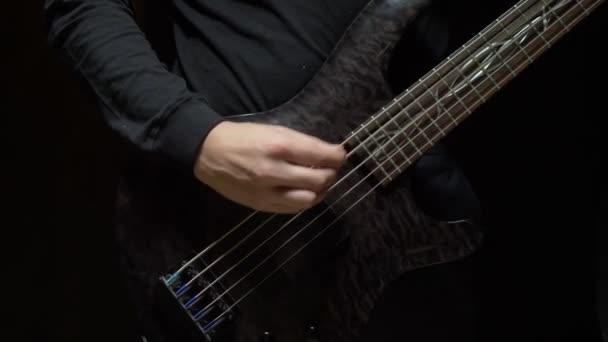 Egy férfi basszusgitározik. Sötét háttér. lassulás