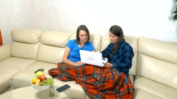 zwei Mädchen sitzen zusammen auf dem Sofa im Wohnzimmer und benutzen Laptop