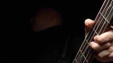 man plays the bass guitar. Dark background. slowmo
