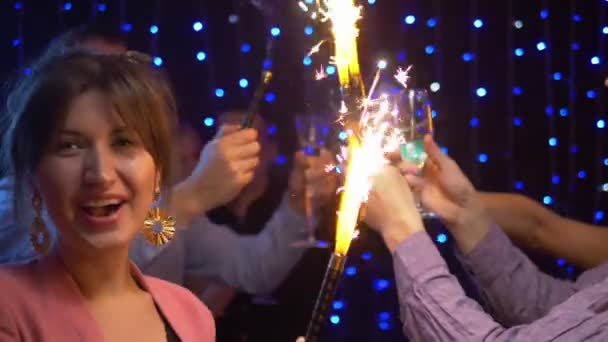 group of friends celebrating at a party, lighting sparklers